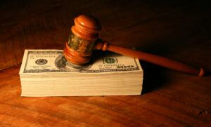Used gavel on a stack of money.